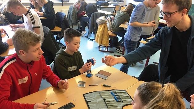 Upps, ist das schwieirg, ein Smartphone zu öffnen. Helmer Wegner bringt genaus Schüler*innen der OBS Uplengen bei. Foto: Werkstatt Zukunft