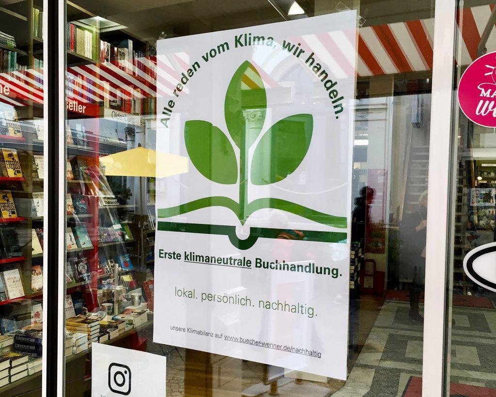 """Poster am Eingang von Bültmann & Gerriets: """"Erste klimaneutrale Buchhandlung""""."""