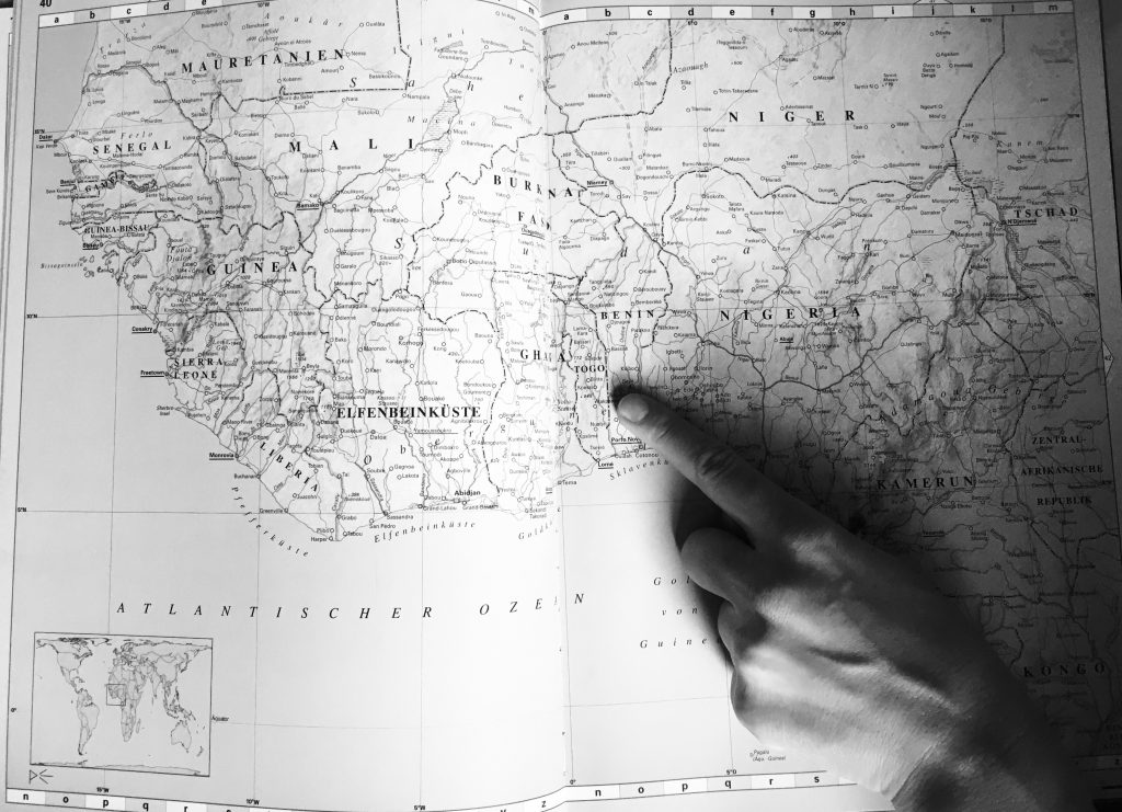Finger auf einer Karte, der auf Togo und Benin zeigt.