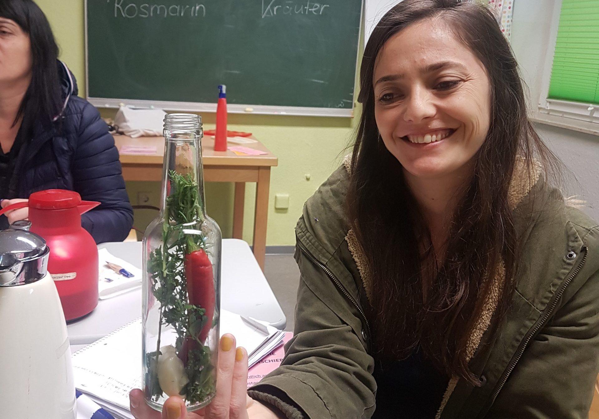 Eine Teilnehmerin präsentiert ihr Kräuteröl.